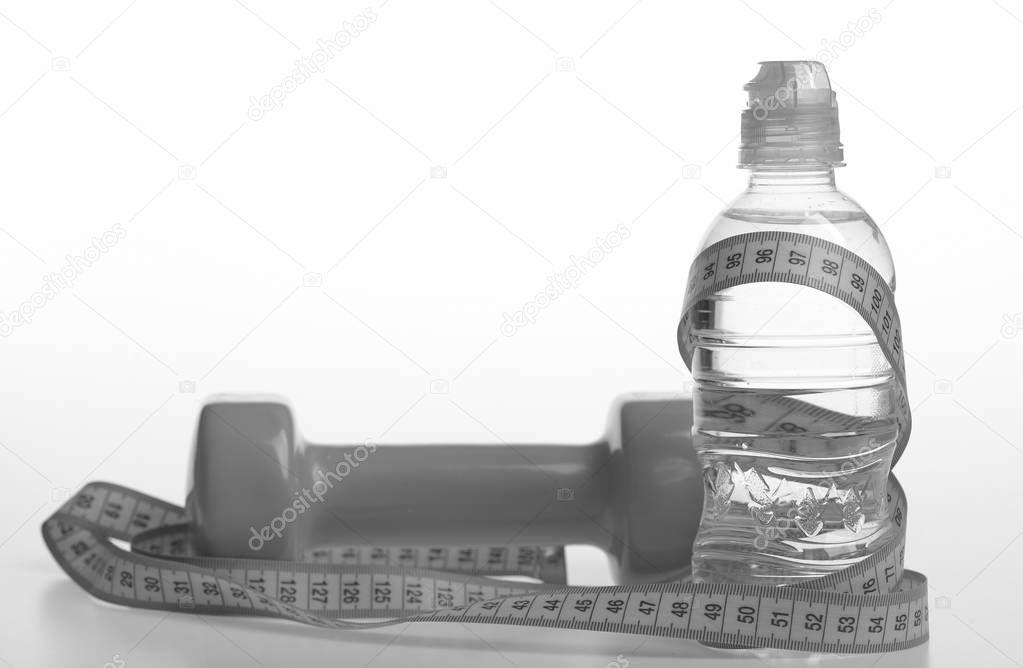 Healthy regime equipment. Water bottle tied with cyan measure tape