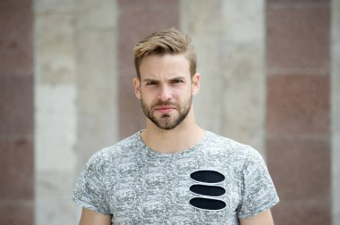 Cool style. Guy bearded attractive care about style and appearance. Man with bristle strict face urban background. Man with beard or unshaven guy looks handsome and cool. Metrosexual concept