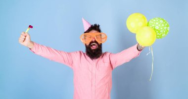 Man with beard and mustache on happy face holds air balloons, light blue background. Party concept. Guy in party hat with holiday attributes celebrates. Hipster in giant glasses celebrating birthday. stock vector