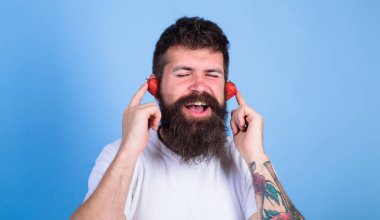 Summer hit concept. Man bearded hipster red ripe strawberry ears as headphones. Summer playlist music. Guy enjoy juicy sound summer hit song music. Hipster beard listen music strawberry earphones