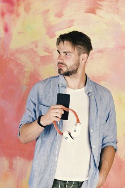 Blue eyed stylish hipster with smartphone. Cheerful teenage dj listening songs via earphones. European guy have fun time. American handsome bearded guy with headphones. Musical lifestyle
