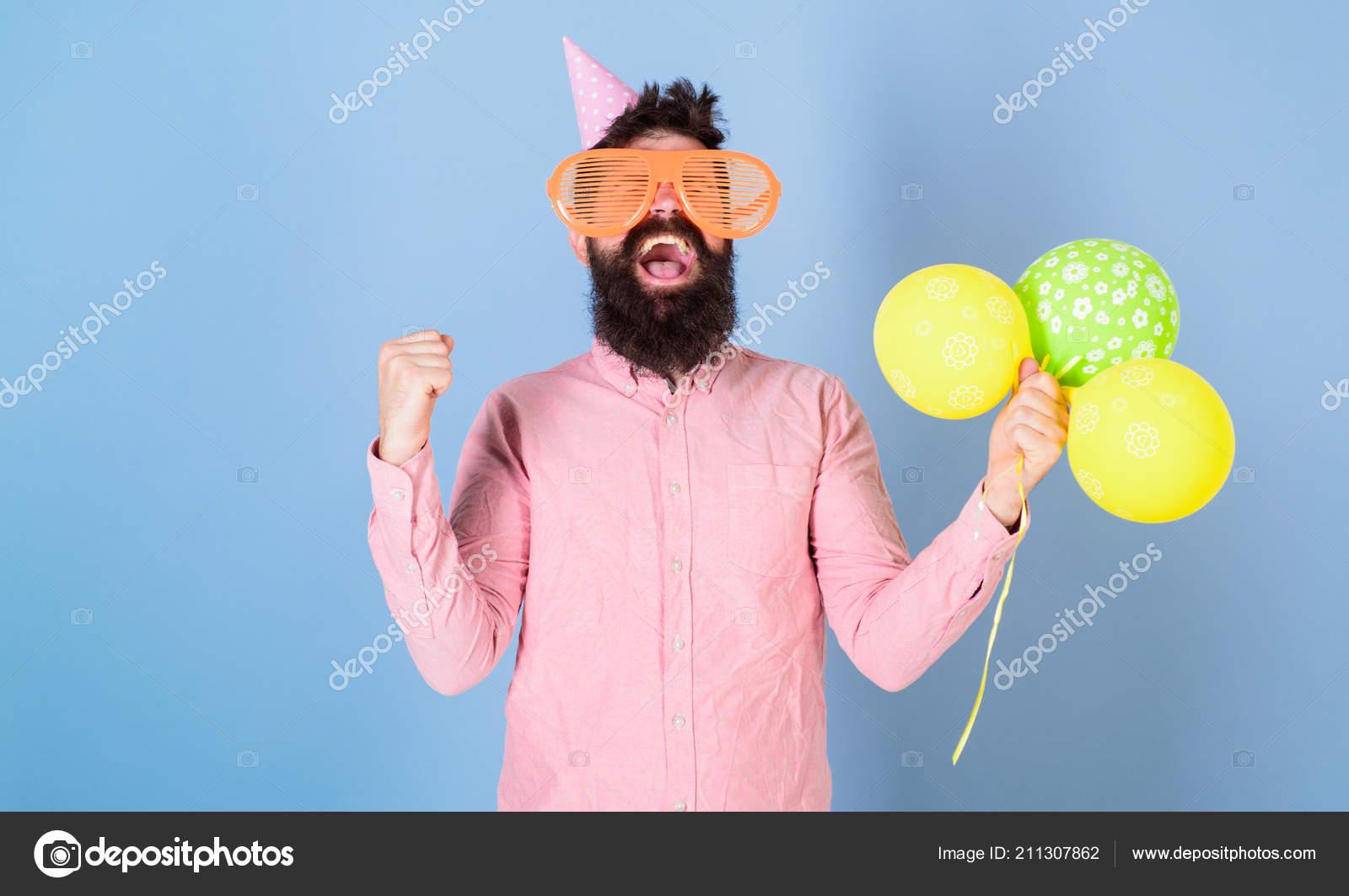 Hipster en gafas gigante celebra cumpleaños. Concepto de celebración.  Hombre con barba en globos de aire cara alegre espera 1afc486ccc7