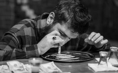 Man with busy face alone at bar counter, sniffing drug. Get high concept. Hipster with beard sniffs cocaine, drug. Guy holds rolled banknote, defocused background.