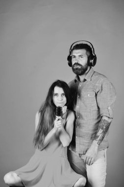 Couple in love wears headphones and hold microphone.
