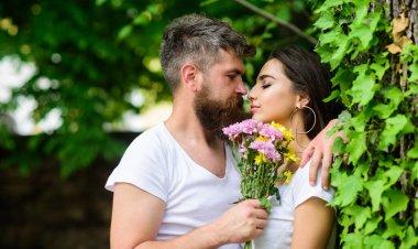 Gentle kiss. Man bearded hipster hugs gorgeous girlfriend. Pleasant romantic kiss. Couple love romantic date nature park background. Love relations romantic feelings. Couple in love going to kiss. stock vector