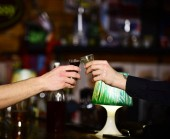 Male hands cheer with glasses of shot or liqueur.