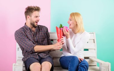 Flowers for her. Man gives bouquet flowers to girlfriend. He guessed her favorite flower. Pleasant surprise for lady. Man woman sit bench romantic date turquoise background. Bouquet favorite flowers