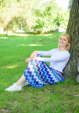 Find peaceful place in park. Give yourself break and enjoy leisure. Girl sit on grass lean on tree trunk relaxing in shadow green nature background. Woman blonde take break relaxing in park