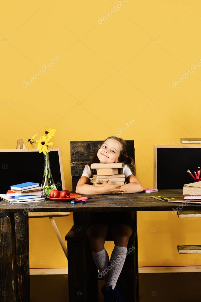 Girl sits at desk with colorful stationery, flowers and fruit