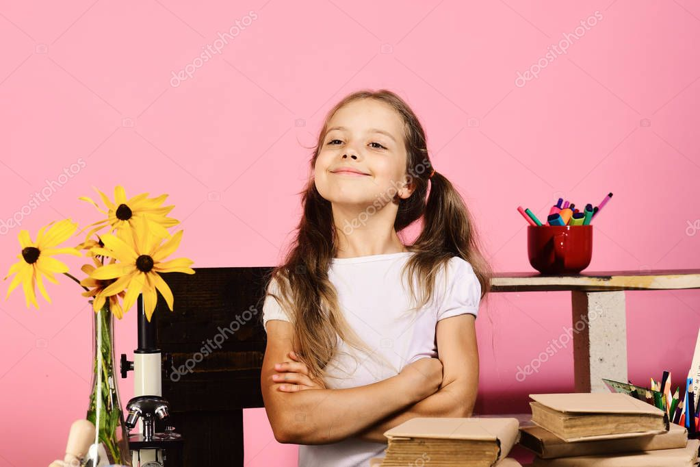 Kid and school supplies on pink wall background