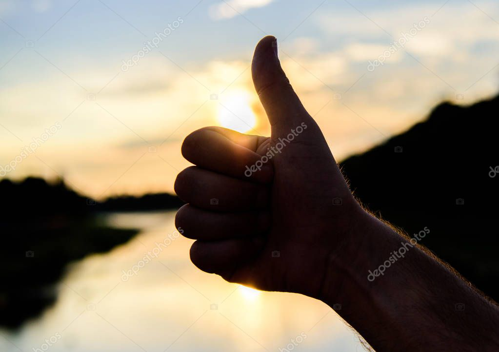 Silhouette thumb up gesture in front of sunset above river water surface. Sunset sunlight romantic atmosphere. Thumbs up gesture sign of best choice approve and accept. Top places to visit in evening