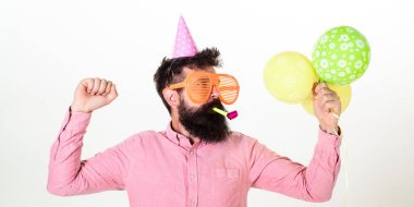 Celebration concept. Guy in party hat with air balloons celebrates. Man with beard and mustache on busy face blows into party horn, white background. Hipster in giant sunglasses celebrating birthday. stock vector