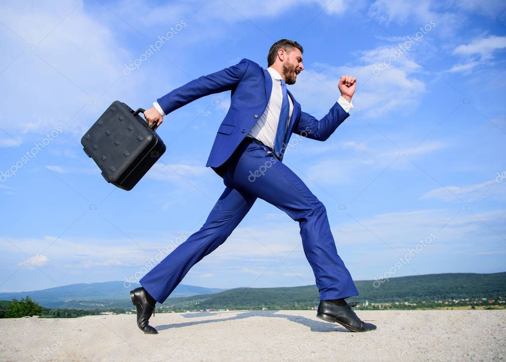Businessman formal suit carries briefcase sky background. Businessman hurrying to business meeting. I will be there in minute. Keep going towards goal. Entrepreneur in motion purposeful expression