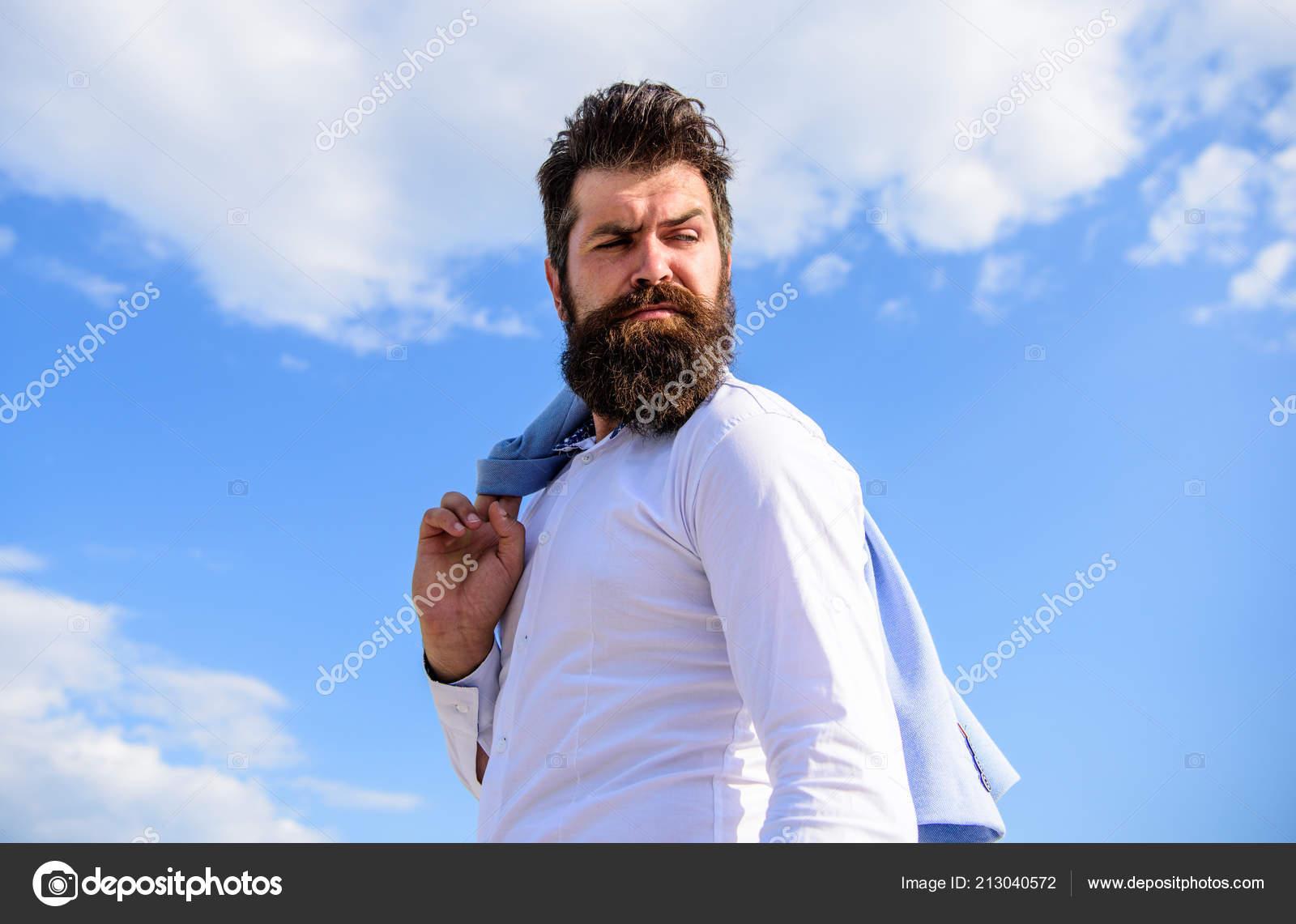 Moda maschile. Aspetto elegante vestito alla moda. Uomo barbuto hipster bianco  vestiti formali sembra forte priorità bassa del cielo. 2e704e8f1b4