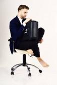 Muž v hezké šaty sedí a drží případ. Kreditní dluhy, podnikatelský úvěr, bankrot koncept.