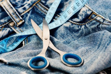 Metal scissors and blue measure tape on jeans. Tailors tools on denim textile. Making clothes and design concept. Jeans belt loops, zipper and pocket, close up, selective focus. stock vector