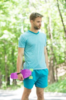 Just try ride once and you will love it. Guy carries penny board ready to ride. Man serious face carries penny board park nature background defocused. Man likes skateboarding and sporty lifestyle