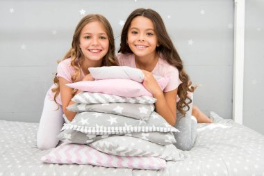Best friends forever. Girls children on bed with cute pillows. Pajamas party concept. Girls just want to have fun. Girlish secrets honest and sincere. Friends kids have nice time pleasant leisure