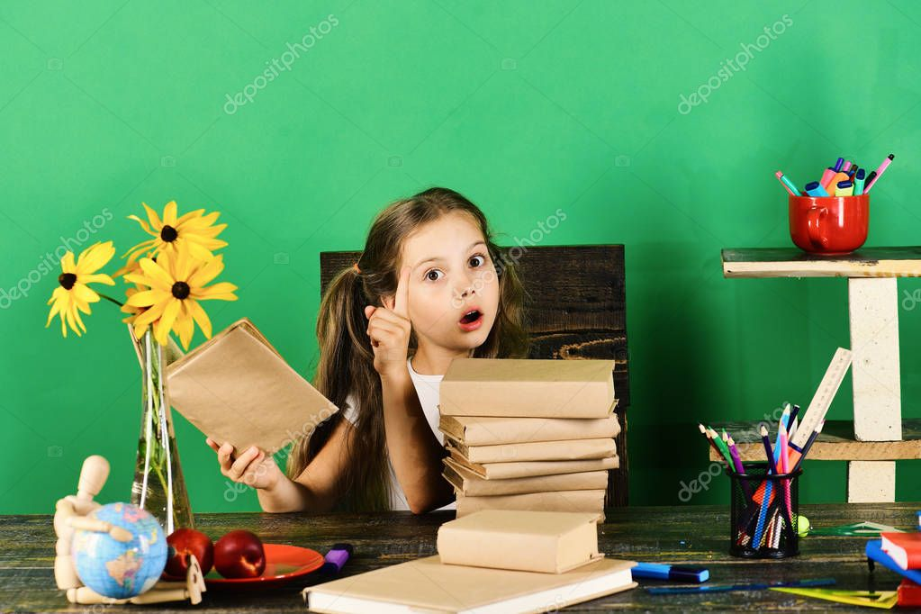 Schoolgirl sits at desk with colorful stationery, books, globe