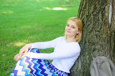 Woman blonde take break relaxing in park. Find peaceful place in park. Give yourself break and enjoy leisure. Girl sit on grass lean on tree trunk relaxing in shadow green nature background