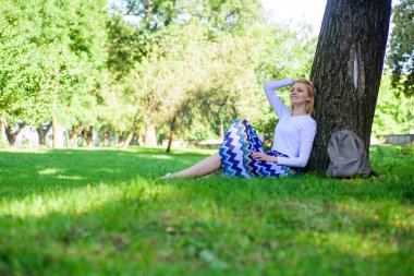 Give yourself break and enjoy leisure. Find peaceful place in park. Girl sit on grass lean on tree trunk relaxing in shadow green nature background. Woman blonde take break relaxing in park