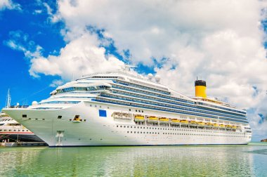 Large luxury cruise ship or liner on sea water and cloudy sky background docked at port of st.Johns, Antigua