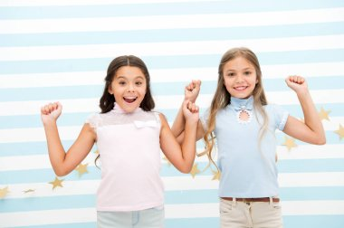 Thrilled moments together. Kids schoolgirls preteens happy together. Girls smiling happy faces excited expression stand striped background. Girls children best friends thrilled about surprising news