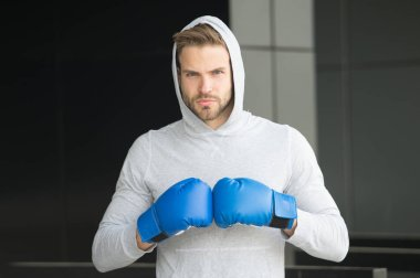 Focused sport goal achievement. Sportsman concentrated training boxing gloves. Athlete concentrated face sport gloves practice fighting skills urban background. Boxer handsome strict coach boxing