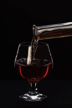 Brandy or cognac filling glass from bottle.