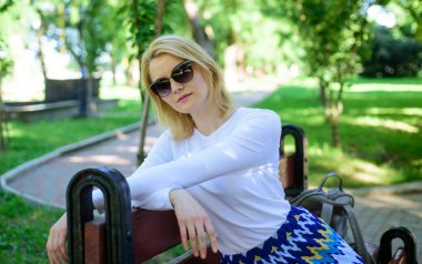 Ways to give yourself break and enjoy leisure. Girl sit bench relaxing in shadow green nature background. Woman blonde take break relaxing in park. Find peaceful place in park. Time for yourself