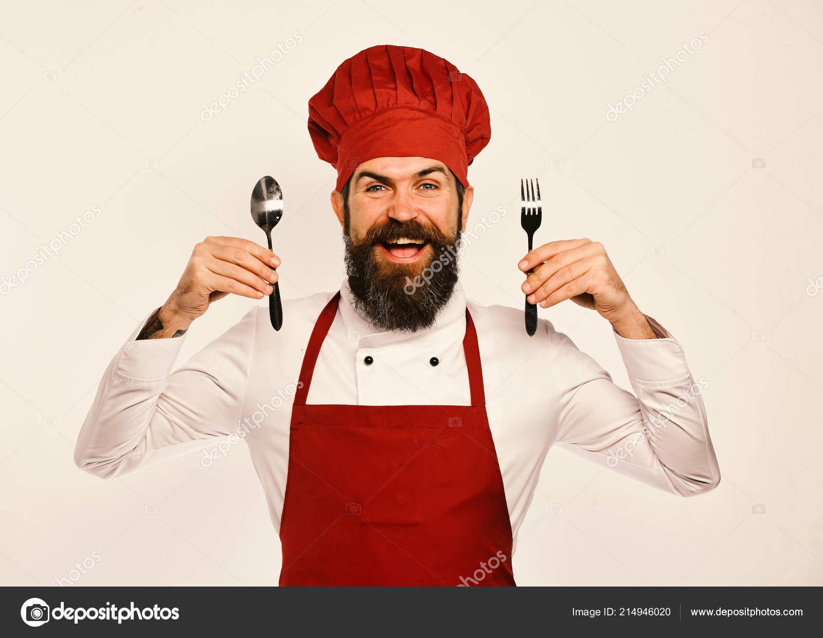 Hombre con barba es tenedor y cuchara sobre fondo blanco. Cocinero con cara  alegre en Borgoña uniforme muestra cubiertos. Chef presenta utensilios de  cocina ... c85a09f970a