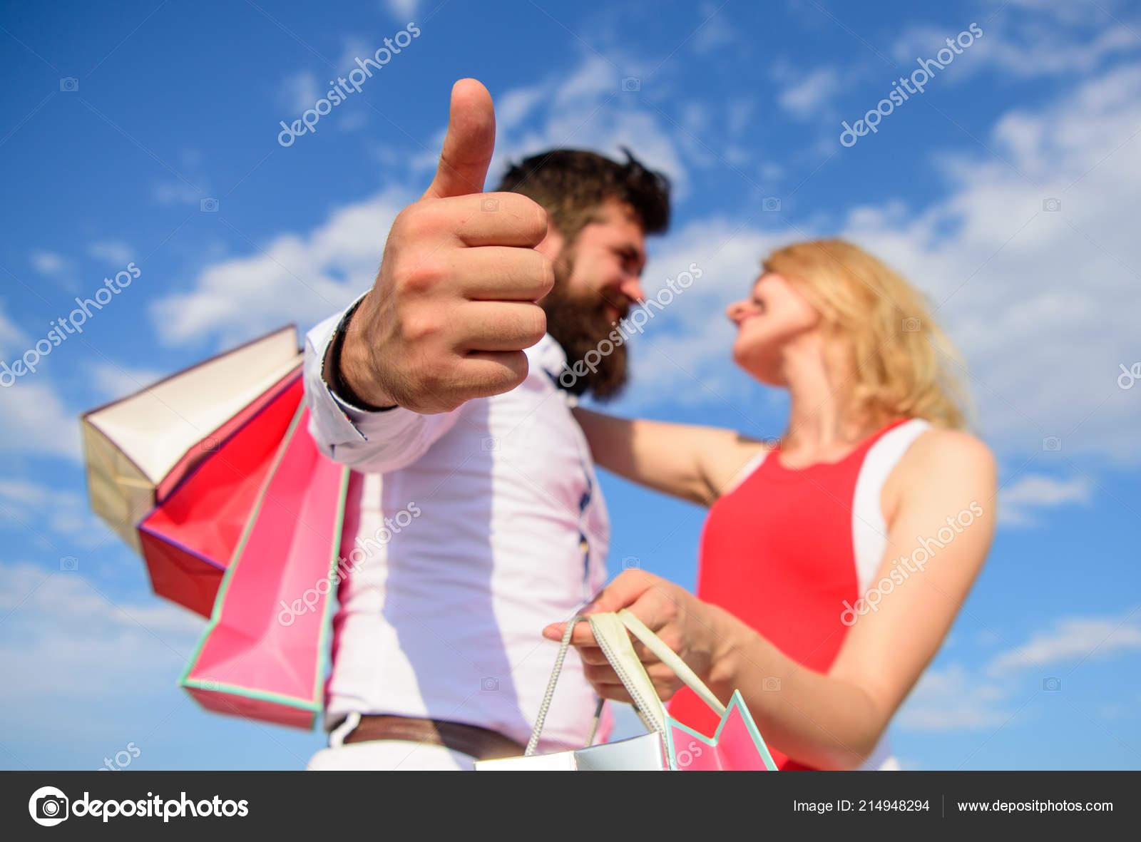 Sfondo blu cielo coccola coppia con borse della spesa. L'uomo con la barba Mostra il pollice sul gesto. Coppia in amore consiglia estate dello shopping. Moglie felice soddisfatta gli acquisti. Lui sa come farla felice — Foto Stock