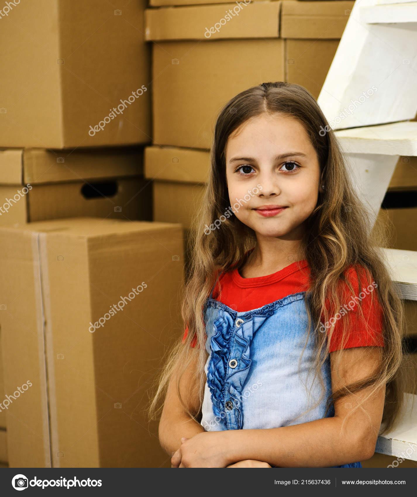 9e2e29fa663 Κορίτσι με δίκαιη κυματιστά μαλλιά σε δωμάτιο ή αποθήκη φόντο. Παιδί  στέκεται από σωρό κουτιά από χαρτόνι και λευκή σκάλα. Μαθήτρια με  χαμογελαστό πρόσωπο ...