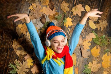Woman knitted hat and scarf listen music headphones. Fall cozy atmosphere. Fall and autumn season. Girl cheerful face listen music lay on wooden background with leaves top view. Autumn melody concept