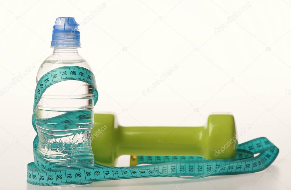 Healthy regime equipment. Water bottle tied with cyan measure tape