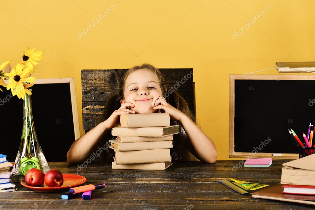 Schoolgirl with happy and funny face expression lies on books
