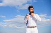 Man bearded hipster formal clothes looks sharp sky background. Reached top. Guy enjoy top achievement. Power and freedom. Hipster with beard and mustache looks attractive fashionable white shirt