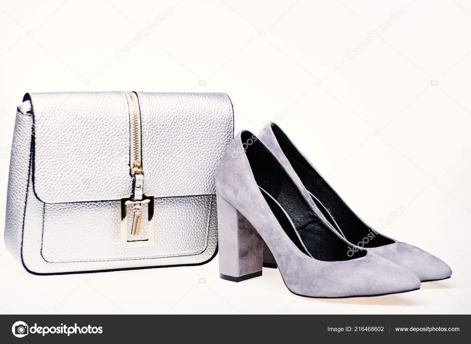597d08a8972 Shoes made out of grey suede on white background. Pair of fashionable high  heeled shoes and silver purse. Footwear for women with thick high heels and  bag