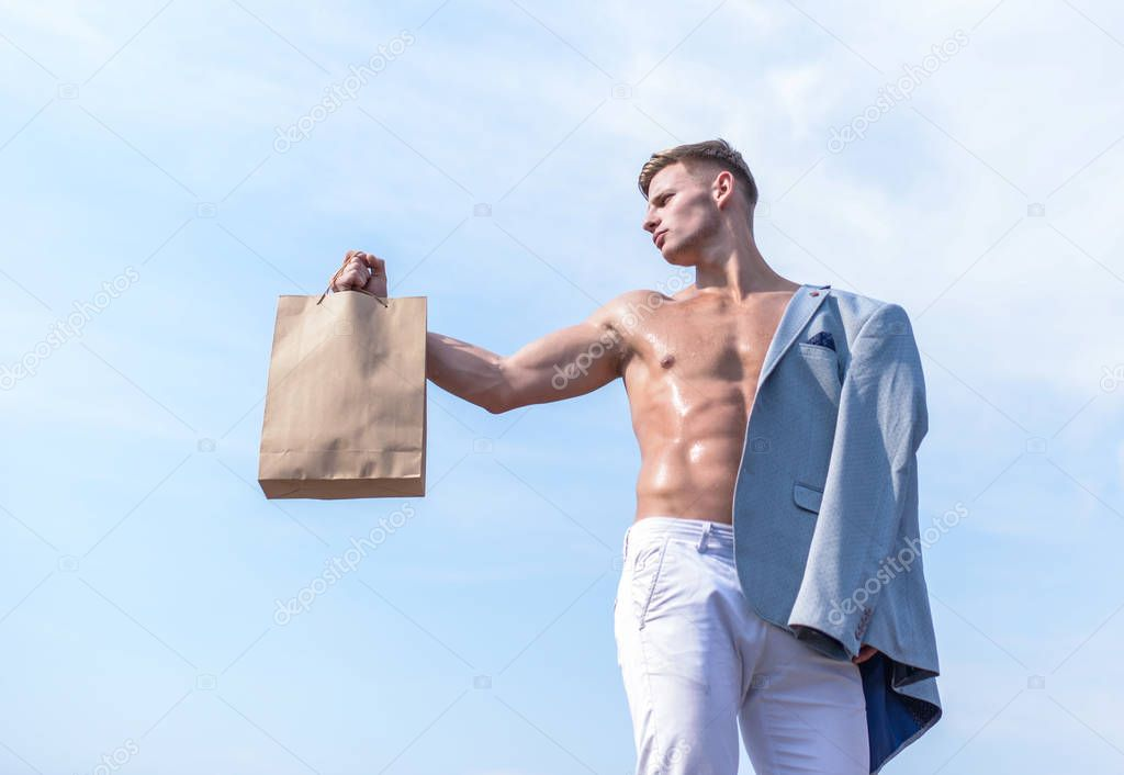 Guy attractive macho carry shopping bag made out of brown paper. Take this package. Sales season. Eco healthy products. Man muscular athlete hold shopping bag sky background. Hot sales and discount