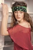 Fotografia ragazza hippie grazioso a bandana verde vicino al frigorifero