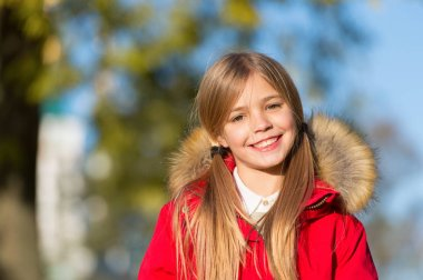 Good mood at fall weather. Kid girl wear coat for fall season. Child cheerful walking wearing warm bright coat or jacket fall sunny day. Girl smiling face fashionable fall coat with hood and fur