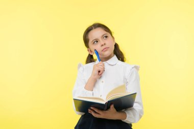 Girl cute schoolgirl in uniform hold book or textbook yellow background. Diligent pupil get knowledge from book. Child wear school uniform prepare for lesson her knowledge. Complex knowledge