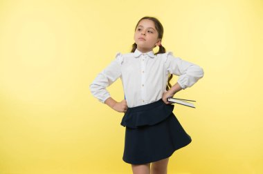 Girl cute schoolgirl in uniform hold book or textbook yellow background. Diligent pupil get knowledge from book. Child wear school uniform prepare for lesson her knowledge. Confident in her knowledge