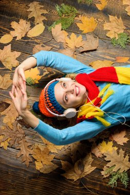 Fall cozy atmosphere. Girl cheerful face listen music lay on wooden background with leaves top view. Autumn melody concept. Woman knitted hat and scarf listen music headphones. Fall and autumn season