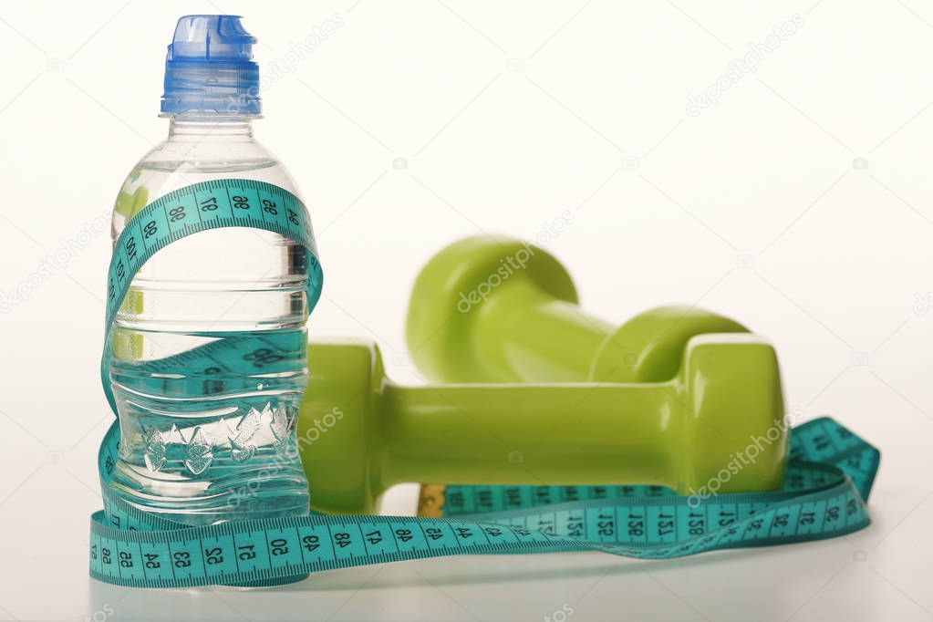 Water bottle tied with cyan measure tape by green dumbbells