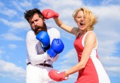 Attack is best defence. Couple in love fighting. Defend your opinion in confrontation. Female attack. Relations family life as everyday struggle. Man and woman fight boxing gloves sky background