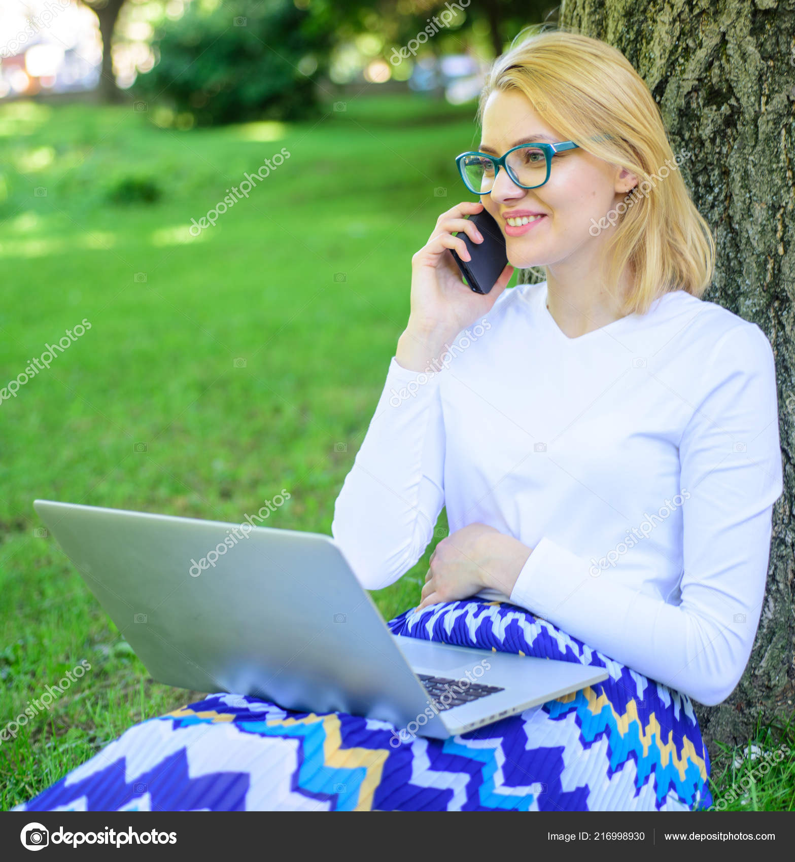 facae7b95 Buy clothes online. Girl sit grass with notebook. Woman with laptop in park  order item on phone. Girl takes advantage of online shopping.