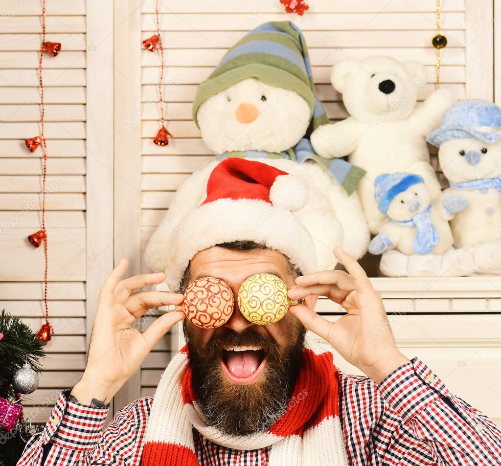 Santa Claus with funny face with tree decoration balls instead of eyes, wooden background. Guy decorates Christmas tree. Man with beard holds golden Christmas decorations. Festivals and decor concept stock vector