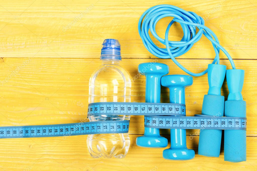 Gym and workout concept. Centimeter tied around sports tools