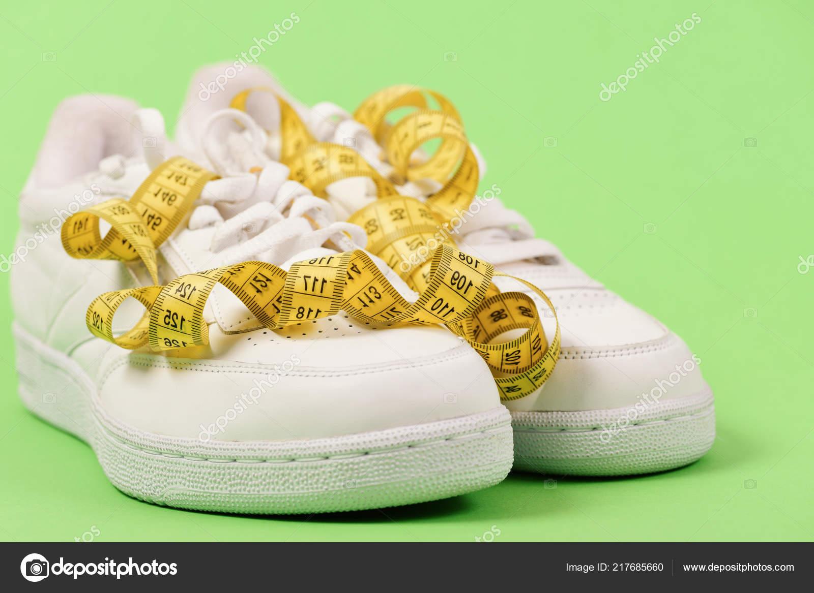 f041473ef74 Αθλητικά παπούτσια και αθλητικό εξοπλισμό για υγιές σχήμα. Έννοια  γυμναστικής και αθλητικών ειδών. Εκατοστό σε κίτρινο χρώμα που κατσαρώνουν  σε λευκό ...